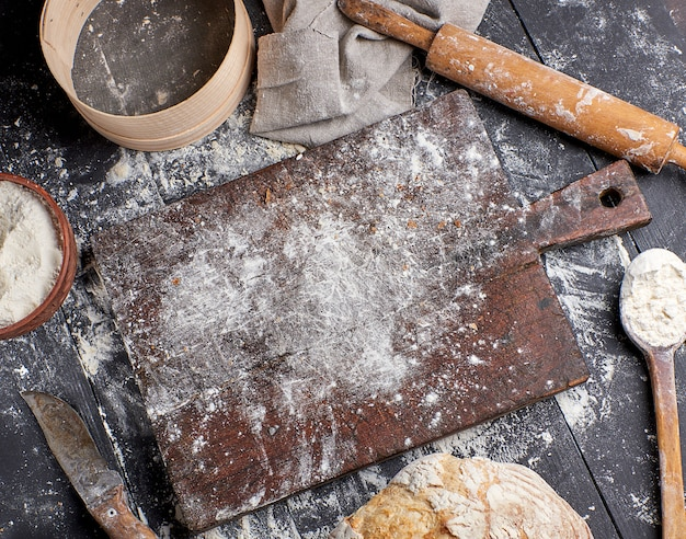 Bread, white wheat flour, wooden rolling pin and old cutting board