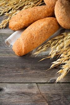 古い木製の背景にスパイクと全粒粉オーツ麦とそば粉をパンします。セレクティブフォーカス。