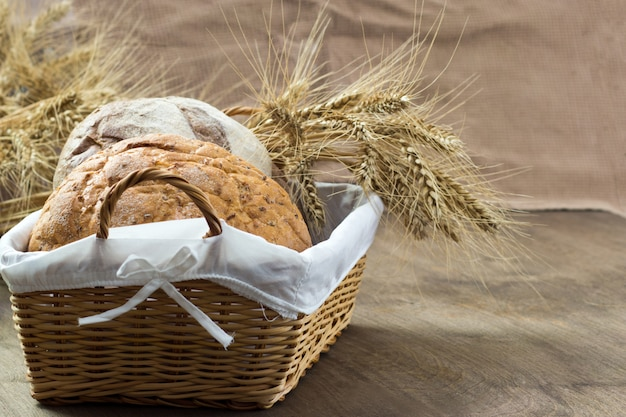 Bread in a wicker basket decorated with ears of corn on wooden table