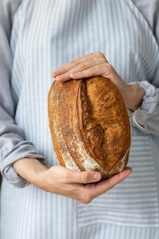 サクサクの皮が付いたパンは美しく、食欲をそそるおいしいパンは木製のまな板の上にあります