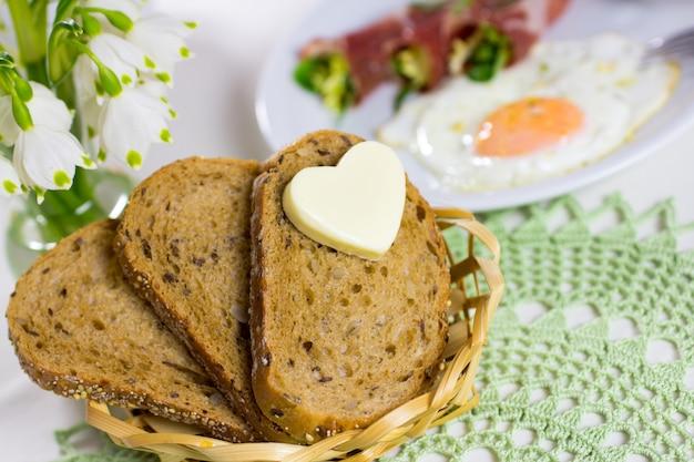 Хлеб с маслом в сердце, яичница с беконом.