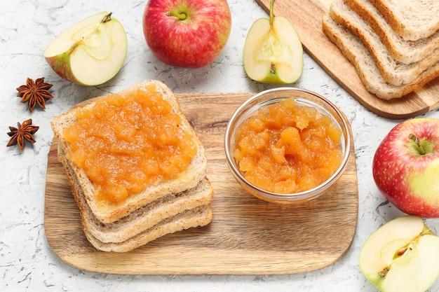 木製のまな板の瓶にリンゴジャムとパン