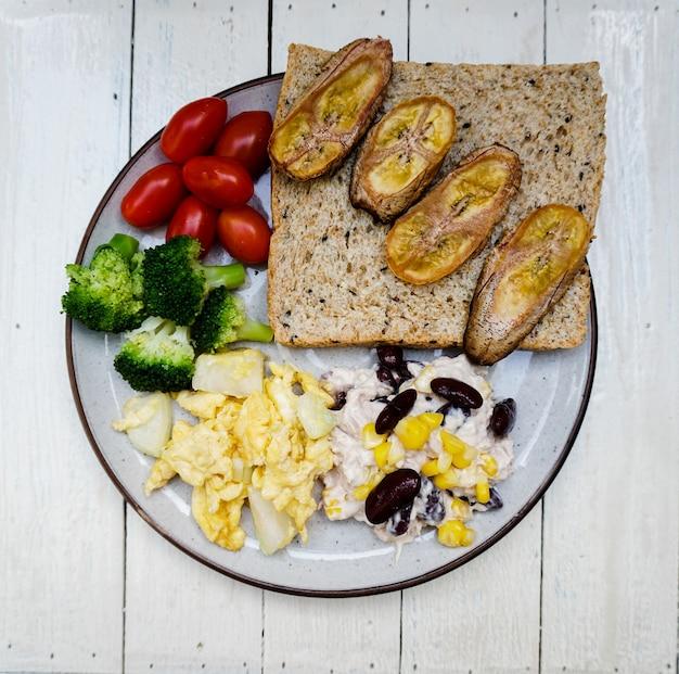 焼きバナナのパンスクランブルエッグ、玉ねぎ、小豆、チェリートマト、ブロッコリーを皿に盛り付けます