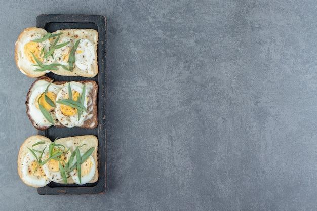 Хлеб с вареными яйцами на черной тарелке.