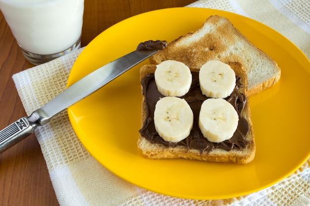 黄色いナプキンにチョコレートクリーム、バナナ、牛乳を添えたパン