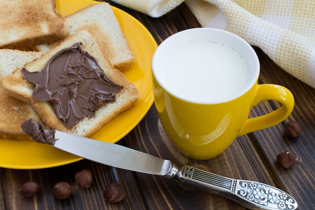 Bread with chocolate cream and milk in the yellow cup