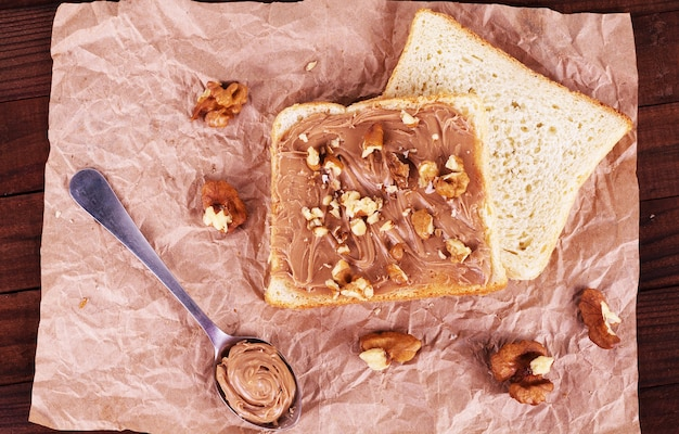 Хлеб с шоколадом, грецкими орехами и ложкой на бумажном фоне