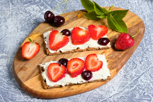 Bread with cottage cheese, fresh strawberries and cherries on a wooden board