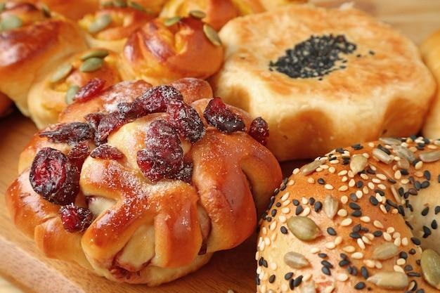 ドライフルーツと他の様々な種類の焼きたてのパンと木製のトレイ