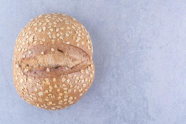 大理石の表面にフレークコーティングされたクラストが付いたパン