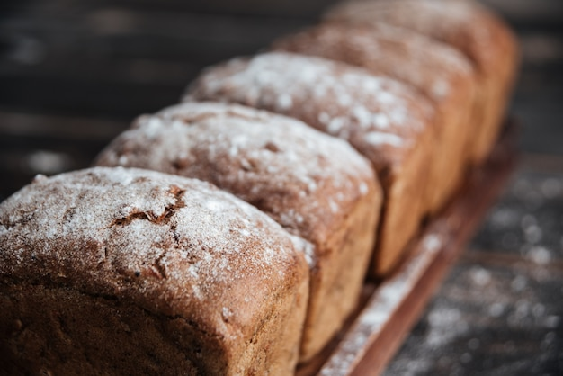 Bread with flour on dark wooden table