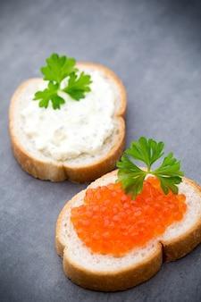 テーブルの上に新鮮なクリームチーズと赤キャビアを添えたパン。