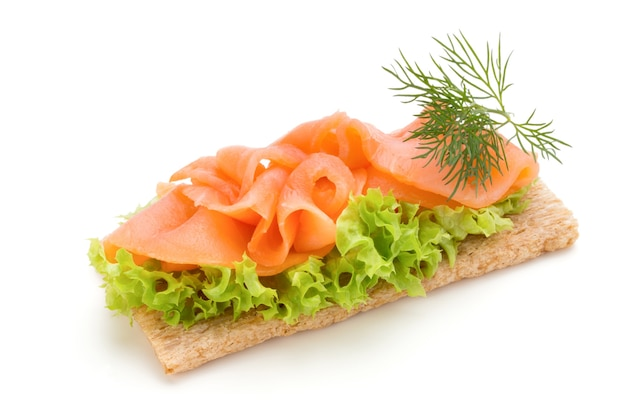Bread with fresh salmon fillet isolated on white surface, top view.