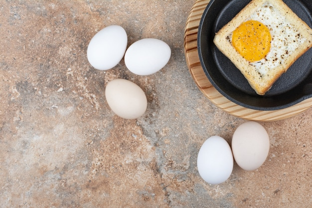 Bread with fried eggs on black plate with raw eggs