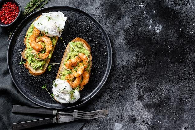 ワカモレ、エビフライ、エビ、卵のパン。黒の背景。上面図。コピースペース