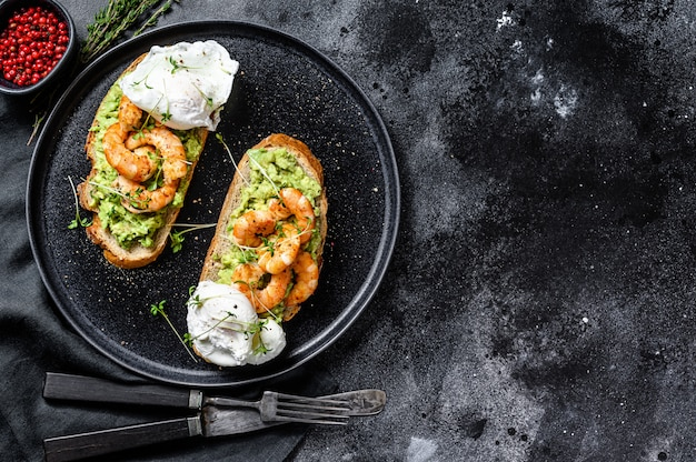 Bread with guacamole, fried shrimp, prawns and egg. black background. top view. copy space