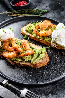 Bread with guacamole, fried shrimp, prawns and egg. black background. top view