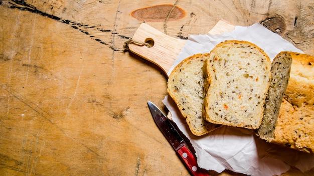 ハーブとナイフを乗せたパン。木製のテーブルの上。テキスト用の空き容量。