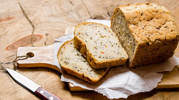 ハーブとナイフを乗せたパン。木製のテーブルの上。
