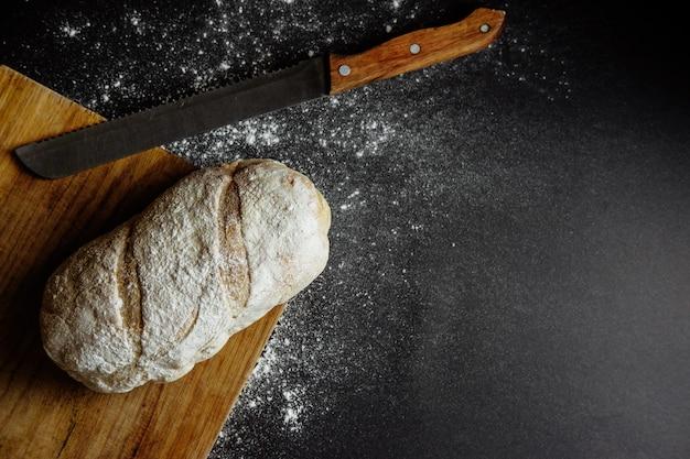 Хлеб с ножом на черной муке на столе