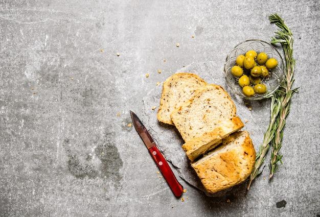 돌 받침대에 올리브와 로즈마리 빵. 돌 테이블에. 텍스트를위한 여유 공간. 평면도