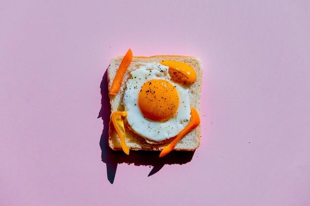 Хлеб с омлетом и перцем на фиолетовом фоне. вид сверху