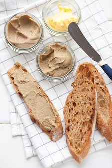 Bread with pate and butter on a textile background.