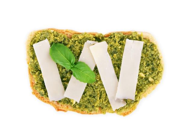 白い背景の上のペスト、バジル、パルメザンチーズの上面図とパン