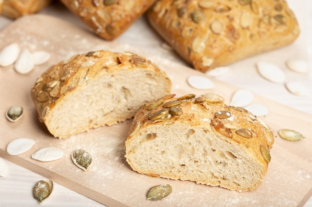 Bread with pumpkin seeds on cutting board