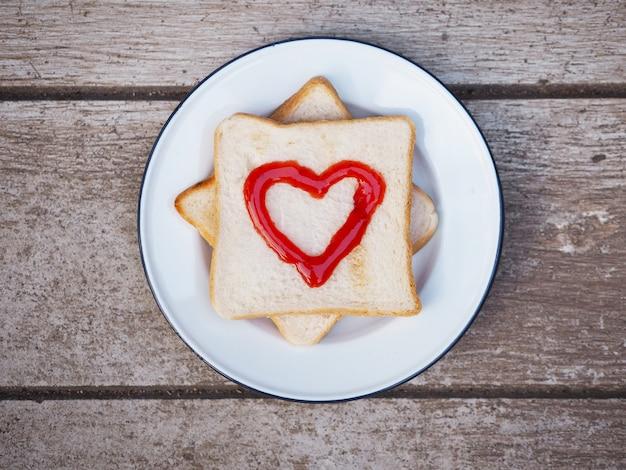 Хлеб с красным фруктовым джемом в форме сердца на белой тарелке