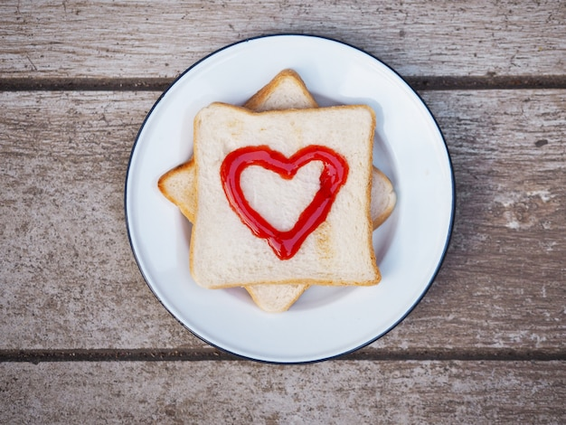 Bread with red fruit jam heart shape on white plate