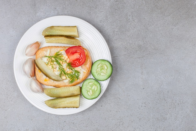 白い皿にスクランブルエッグとピクルスのパン