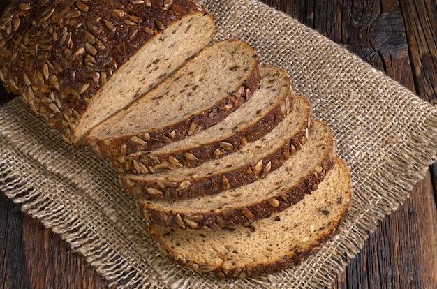 種子と古い木製のテーブルにドライフルーツのパン