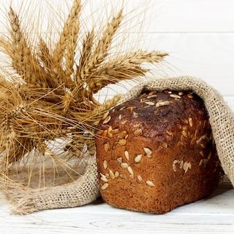 木製のテーブルに種子と小麦の穂とパン
