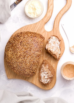 Bread with sesame seeds on a wooden board next to cut pieces with buttered peanut butter. breakfast