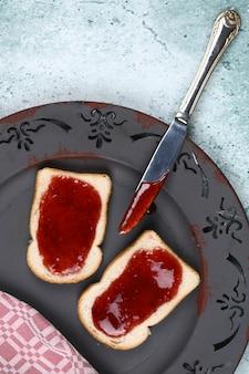 회색 접시에 딸기 잼 빵입니다.