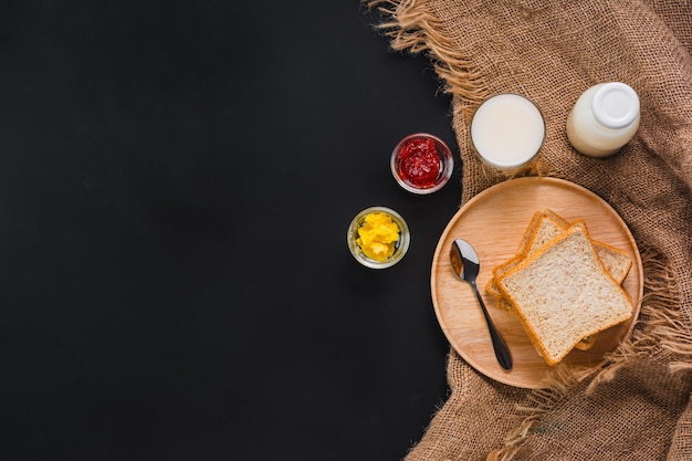Bread with strawberry jam, milk, and butter on black background, top view