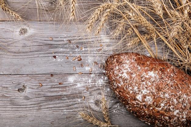 テクスチャード加工の木製の背景にヒマワリの種とパン。素朴なスタイル