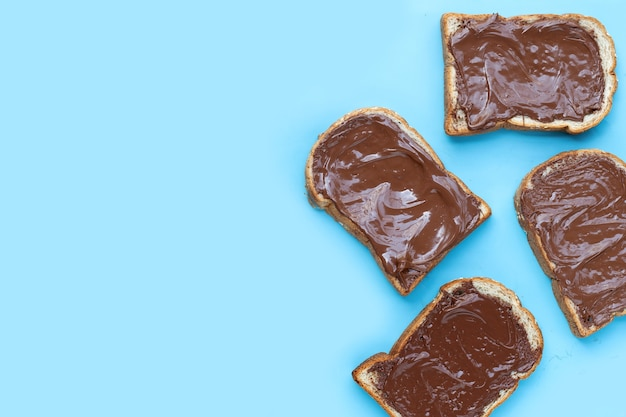 Bread with sweet chocolate hazelnut on blue background.