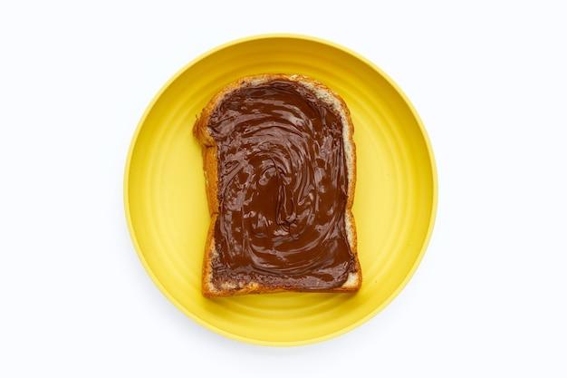 Хлеб со сладким шоколадным лесным орехом в желтой тарелке на белом