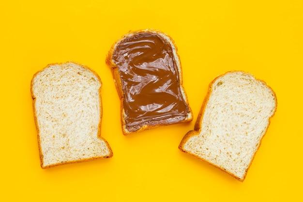 黄色の背景に甘いチョコレートヘーゼルナッツとパン。