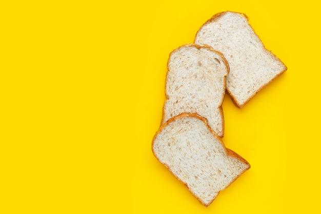 黄色の背景に甘いチョコレートヘーゼルナッツとパン。 Premium写真