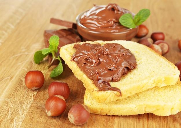 木製の背景に広がる甘いチョコレートヘーゼルナッツとパン
