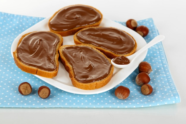 Bread with sweet chocolate hazelnut spread on plate on white