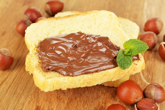 Bread with sweet chocolate hazelnut spread on wooden
