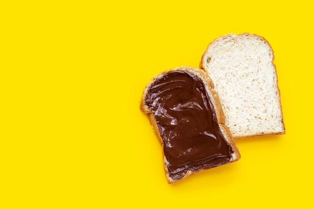 Bread with sweet chocolate hazelnut on yellow background.