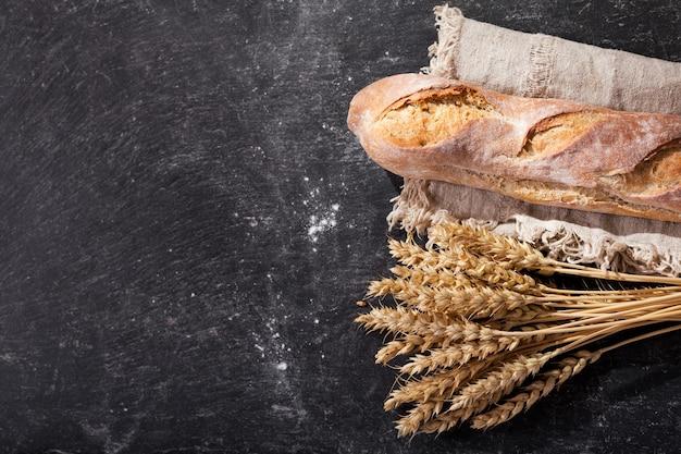暗い板に小麦の穂が付いているパン、上面図