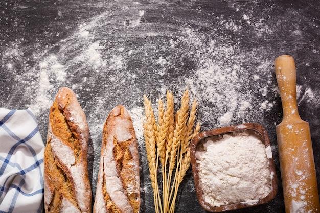 暗いボード上の小麦の穂とパン、上面図