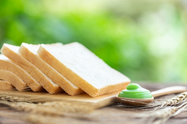 Bread on wooden table with green blur light background. food concept