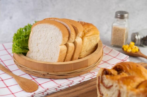 Pane in un vassoio di legno su un panno rosso e bianco.